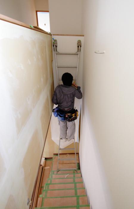 岡山市中区に建築中の中井の家の階段にクロスを貼っています