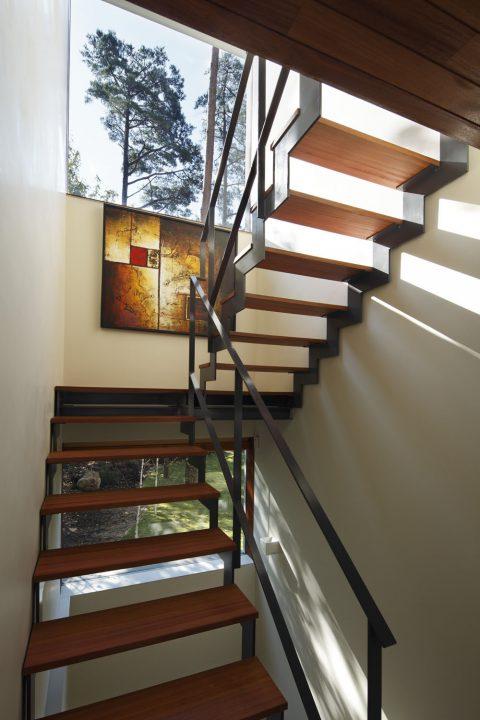 森の中に完成した絶景を楽しむ別荘、鉄骨階段のすきまから光が入る階段スペース