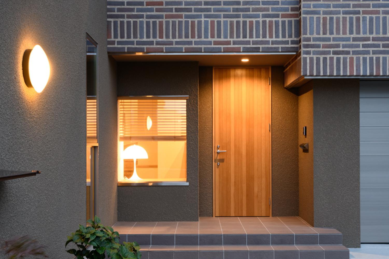 木製ドアとタイルやステンレスの組み合わせが新しい玄関