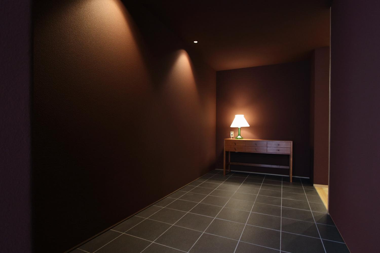 ガーネット色の吹付壁にダークグレーのタイルを合わせたシックなフラット玄関
