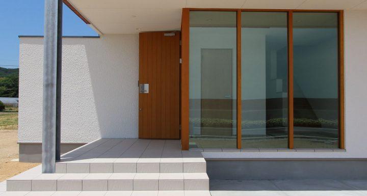 海沿いに立つ注文住宅、爽やかなガラス張りとタイルの玄関
