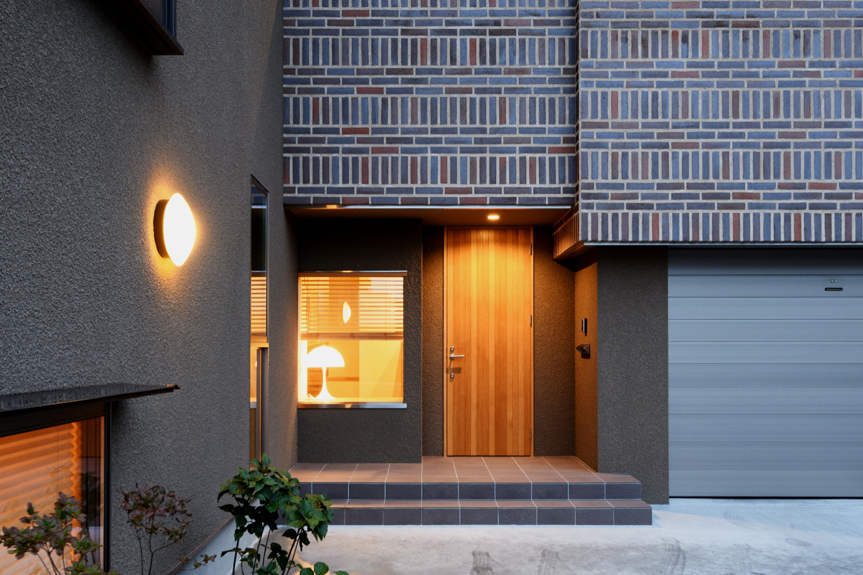 タイルと木 ステンレスなどの異素材を贅沢に合わせたモダンで重厚感のある玄関