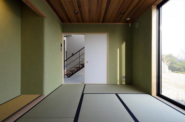 緑の壁と板張りの天井のモダンな和室