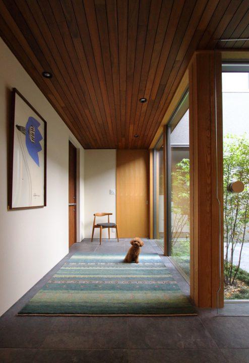 中庭を眺める明るい玄関と愛犬