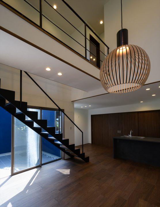 北欧の木製照明や鉄骨階段、モルタル風のキッチンなど、シックな印象のLDK