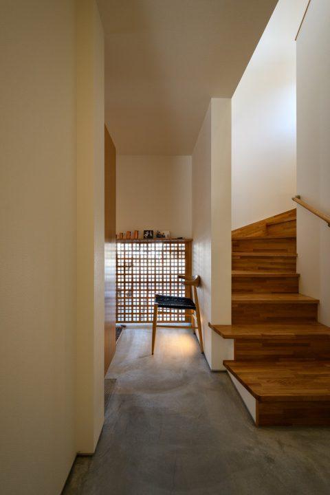 早島に完成した注文住宅、大屋根の家の格子窓から光が漏れる玄関