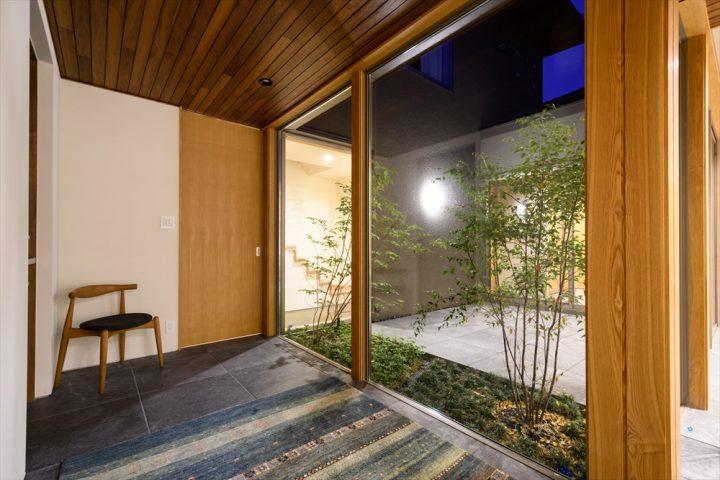 中庭のライトアップが見える夜の玄関
