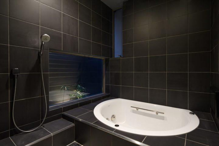 黒いタイルの広々とした浴室