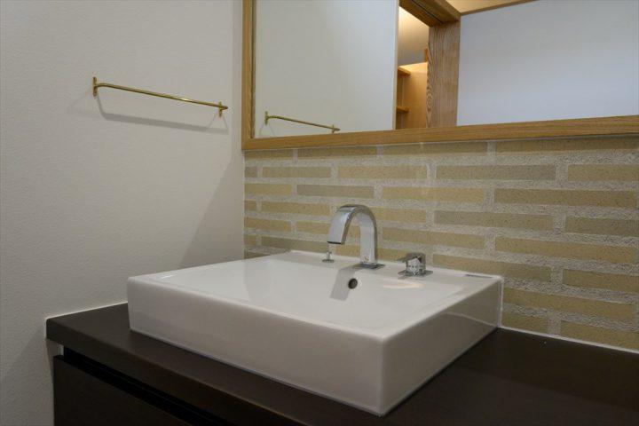 白いタイルと大きな鏡を貼った洗面室