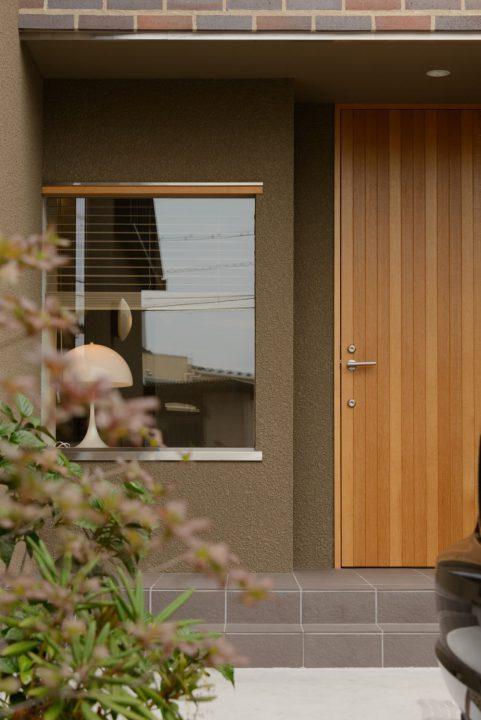 タイルと木、ステンレスなどの異素材を贅沢に組み合わせたモダンな玄関