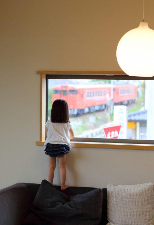 リビング窓から電車を見る女の子