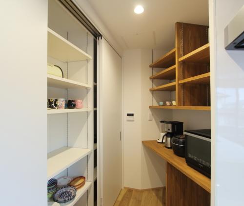 キッチン奥には両面に収納棚を設置しました
