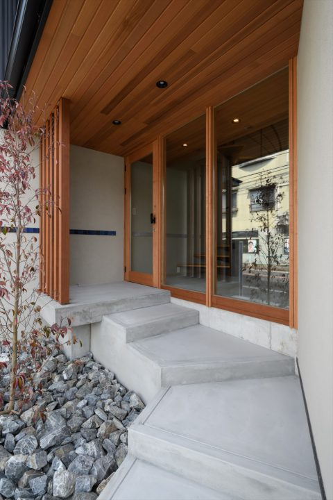 木とモルタルでシンプルに仕上げた玄関アプローチと植栽
