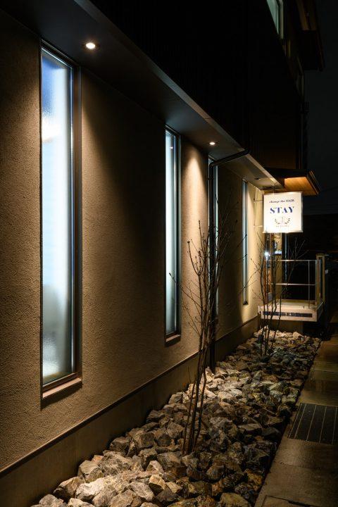 縦長の窓と照明を交互に配置し、美しいライトアップの夜の外観