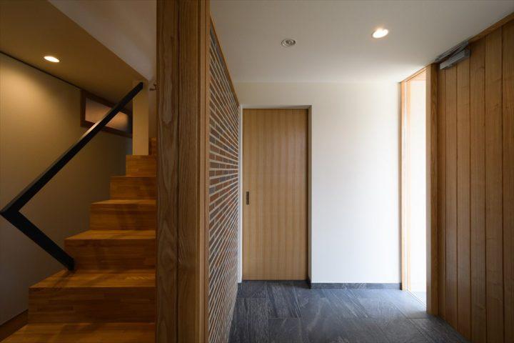 岡山市の注文住宅Wall Dsignのタイル壁のフラットな玄関