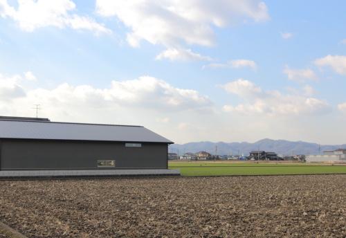 岡山市南区藤田に建築中の田園に浮かぶ平屋、グレーでモダンな外観