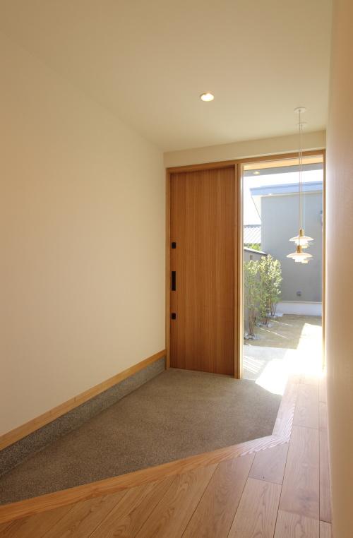 ななめ框に木製ドアとペンダント照明のオシャレな玄関