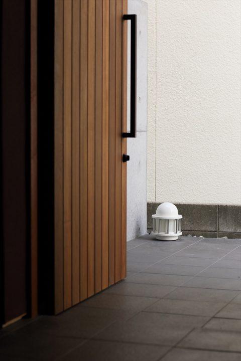 木製ドアとダークグレータイルにコンクリート壁のカッコイイエントランス