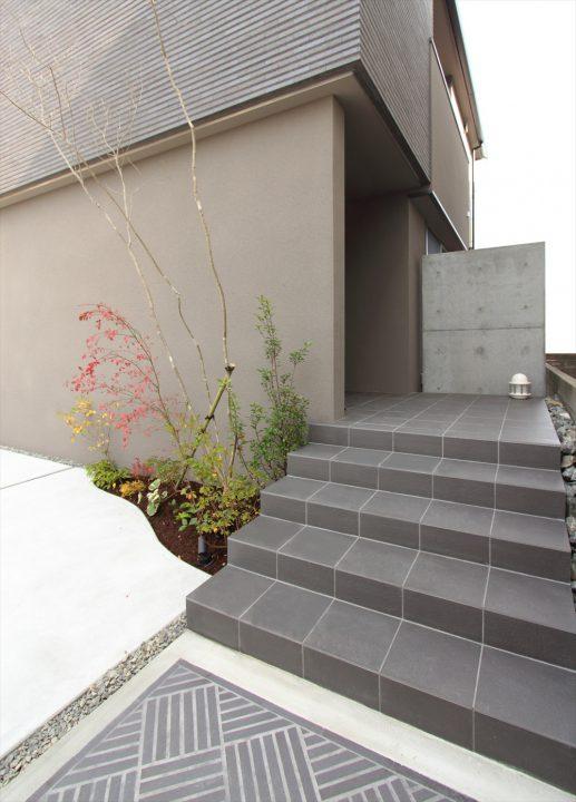 グレータイルと植栽のシックなアプローチ