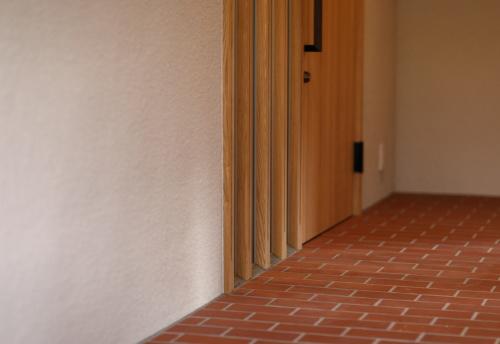 木製建具と赤いタイルのモダンな玄関