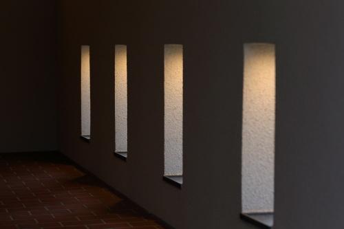 贅沢な奥行のあるタイルのアプローチと光が漏れる小さな窓