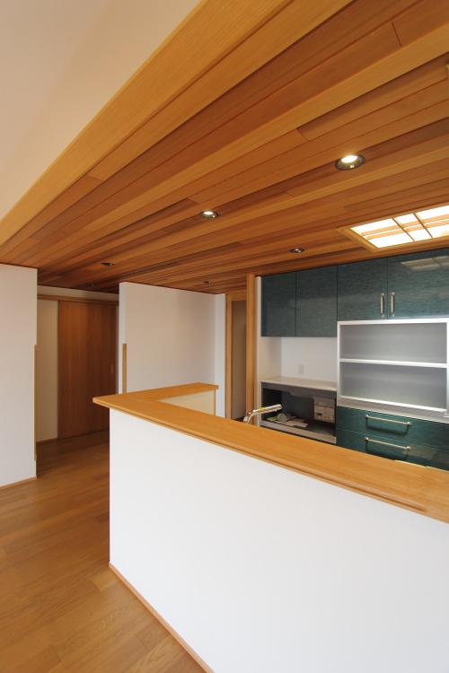 倉敷市に完成した海を眺めながら暮らす平屋の家、板張りの天井と深い緑色の落ち着くキッチン